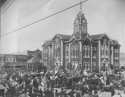Hunt County Courthouse on San Jacinto Day 1917. A record-breaking crowd gathered to hear Texas Governor James E. Ferguson speak as the large U. S. flag was raised over the courthouse. Notice the over-whelming number of white males in the crowd.