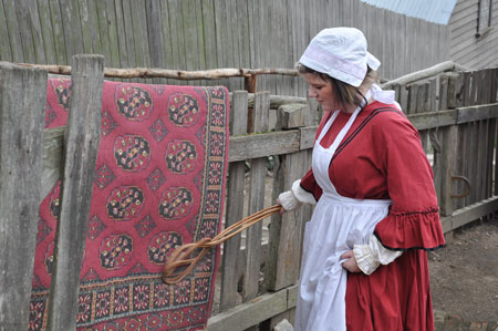 "Beating a rug in the mid 1850s. The object in her hand was known as a ""carpet beater"" and took a fairly strong girl to rid the rug of the accumulation of dirt from the winter. (Sovereign Hill Education Blog, servant-carpet-beating.)"